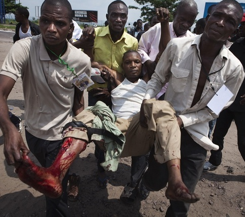 An opposition supporter shot by presidential guard is carried in Congo's capital Kinshasa