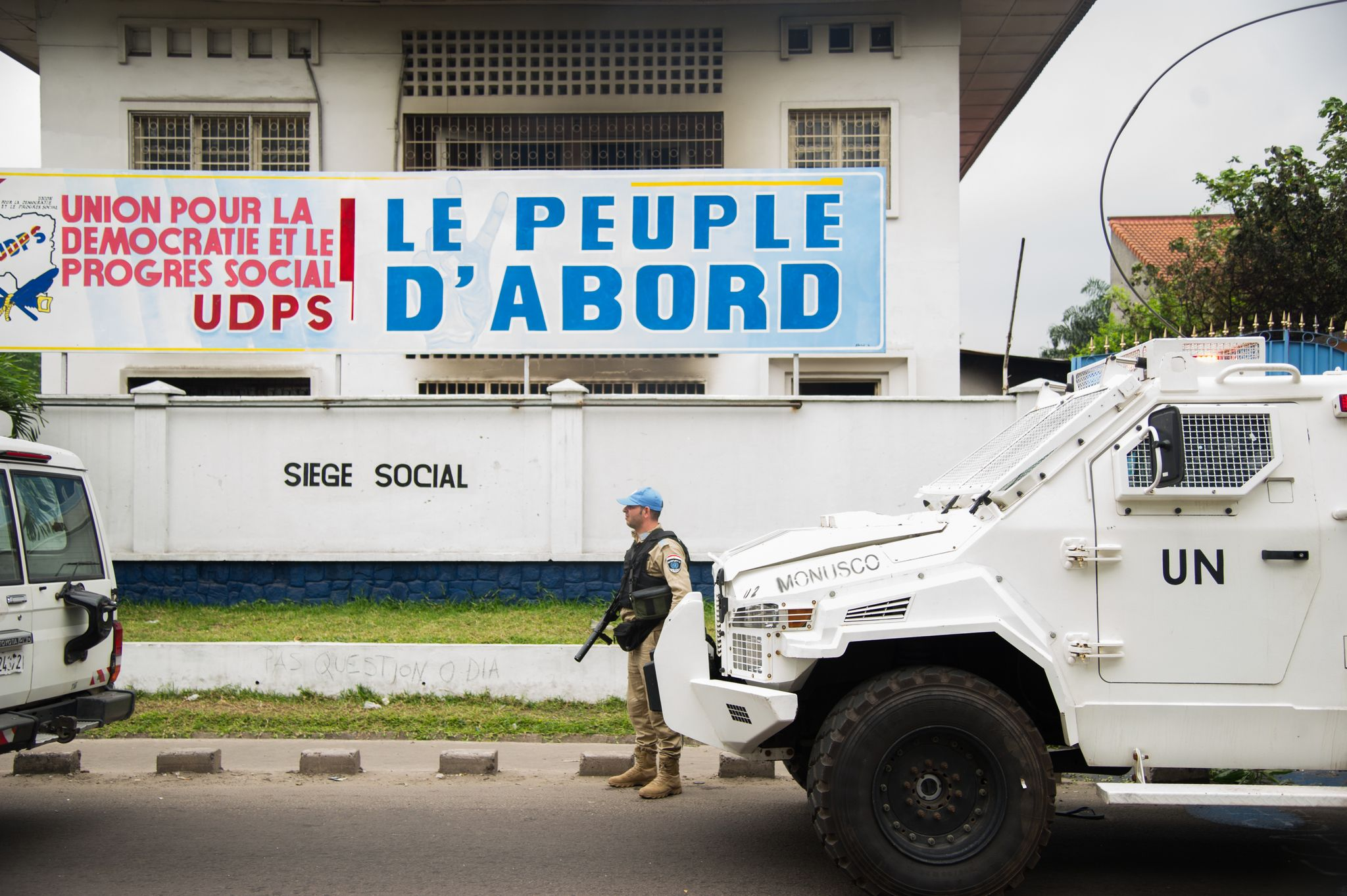 A peacekeeper of the MONUSCO, the UN mission in the Democratic Republic of Congo, stands guard on September 20, 2016 in front of the offices of the main opposition Union for Democracy and Social Progress (UDPS) party which were torched overnight and early on September 20, 2016, in Kinshasa.At least two burnt bodies could be seen in the fire-ravaged offices of the UDPS, while two other people were burnt alive and one person injured, they said. The fresh violence came after a bloody day on September 19, 2016 during which opposition groups said more than 50 people had died. Violence of September 19, 2016 started just before an opposition rally by demonstrators who fear Kabila -- who has ruled the Democratic Republic of Congo since 2001 -- is planning to extend his rule unconstitutionally. / AFP PHOTO / JUNIOR D.KANNAH